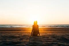 Η συνεδρίαση κοριτσιών στην παραλία στο ηλιοβασίλεμα στοκ φωτογραφίες με δικαίωμα ελεύθερης χρήσης