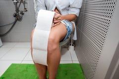 Η συνεδρίαση κοριτσιών στην τουαλέτα κρατά το χαρτί τουαλέτας Η έννοι στοκ φωτογραφία με δικαίωμα ελεύθερης χρήσης