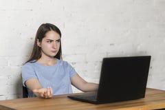 Η συνεδρίαση κοριτσιών στον πίνακα, εξετάζει αγανακτισμένα την οθόνη lap-top στοκ φωτογραφία με δικαίωμα ελεύθερης χρήσης