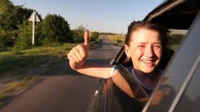 Η συνεδρίαση κοριτσιών στο κάθισμα αυτοκινήτων κοιτάζει από το παράθυρο χαμογελώντας και η παρουσίαση συμπαθεί με το χέρι της φιλμ μικρού μήκους