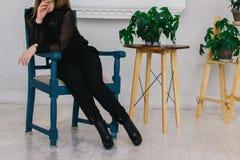 Η συνεδρίαση κοριτσιών στο υψηλό ξύλινο σκαμνί σε ένα γκρίζο υπόβαθρο στο μαύρο πουλόβερ και τα υψηλά τακούνια έδρες ξύλινες Ένα  στοκ φωτογραφίες