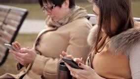 Η συνεδρίαση μητέρων και κορών στο πάρκο επικοινωνεί και χρησιμοποιεί ένα κινητό τηλέφωνο Φύση, σχέσεις απόθεμα βίντεο