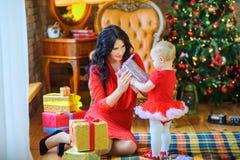 Η συνεδρίαση μητέρων στο πάτωμα κοντά στο χριστουγεννιάτικο δέντρο δίνει ένα δώρο στην αγαπημένη κόρη της στοκ φωτογραφίες με δικαίωμα ελεύθερης χρήσης