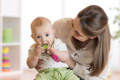 Η συνεδρίαση μωρών στα γόνατα mom δαγκώνει το παιχνίδι στοκ φωτογραφίες με δικαίωμα ελεύθερης χρήσης