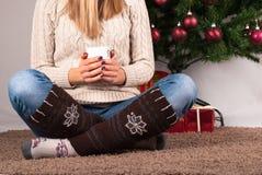 Η συνεδρίαση νέων κοριτσιών στο φλιτζάνι του καφέ πατωμάτων και εκμετάλλευσης, στο υπόβαθρο είναι χριστουγεννιάτικο δέντρο και πα Στοκ φωτογραφίες με δικαίωμα ελεύθερης χρήσης