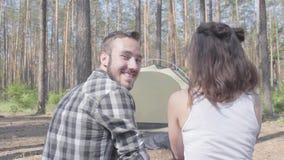 Η συνεδρίαση νεαρών άνδρων και γυναικών η μια κοντά στην άλλη με τις πλάτες στη κάμερα στο δάσος η σκηνή στο υπόβαθρο Το άτομο απόθεμα βίντεο