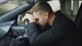 Η συνεδρίαση νεαρών άνδρων μέσα στο αυτοκίνητο είναι πολύ και τονισμένη Στοκ φωτογραφία με δικαίωμα ελεύθερης χρήσης