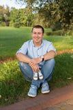 Η συνεδρίαση νεαρών άνδρων στη χλόη στο πάρκο και κρατά τα πάνινα παπούτσια για νεογέννητο στοκ εικόνες με δικαίωμα ελεύθερης χρήσης