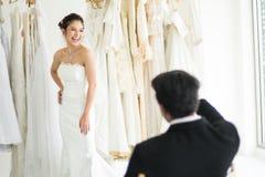 Η συνεδρίαση νεόνυμφων και φαίνεται η νύφη του που δοκιμάζει τα φορέματα στοκ εικόνες με δικαίωμα ελεύθερης χρήσης