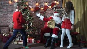 Η συνεδρίαση Άγιου Βασίλη σε μια καρέκλα κοντά σε ένα χριστουγεννιάτικο δέντρο συναντά τα παιδιά κίνηση αργή απόθεμα βίντεο