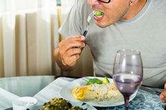 Η συνεδρίαση ατόμων από το αριστοκρατικό γεύμα που θέτει την κατανάλωση του δικράνου με το μπρόκολο, crepe καλυμμένος στην άσπρη  στοκ εικόνες