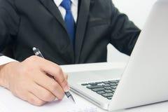 Η συνεδρίαση επιχειρηματιών που λειτουργεί στο lap-top και γράφει τη σημείωση Στοκ Εικόνες
