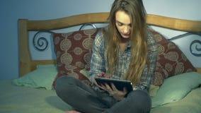 Η συνεδρίαση κοριτσιών στο κρεβάτι και κρατά μια ηλεκτρονική ταμπλέτα απόθεμα βίντεο