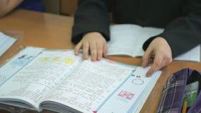 Η συνεδρίαση μαθητών στο γραφείο κτυπά τις σελίδες του σχολικού βιβλίου απόθεμα βίντεο
