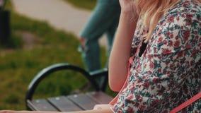 Η συνεδρίαση μητέρων στον πάγκο και μιλά στο τηλέφωνο στο πάρκο Ταλαντεμένος μεταφορά μωρών απόθεμα βίντεο