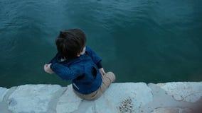 Η συνεδρίαση μικρών παιδιών στην αποβάθρα ρίχνει τις πέτρες στο νερό υπαίθρια απόθεμα βίντεο