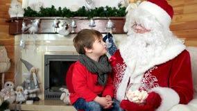 Η συνεδρίαση μικρών παιδιών στην περιτύλιξη santa ` s, παιδί που επισκέπτεται τη χειμερινή κατοικία Άγιου Βασίλη και λέει τις επι απόθεμα βίντεο
