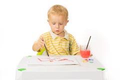 Η συνεδρίαση μικρών παιδιών στον πίνακα και σύρει μια ζωγραφική βουρτσών Στοκ Εικόνες