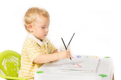 Η συνεδρίαση μικρών παιδιών στον πίνακα και σύρει μια ζωγραφική βουρτσών Στοκ Φωτογραφία