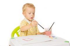 Η συνεδρίαση μικρών παιδιών στον πίνακα και σύρει μια ζωγραφική βουρτσών Στοκ φωτογραφία με δικαίωμα ελεύθερης χρήσης