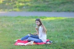 Η συνεδρίαση νέων κοριτσιών στη χλόη στο πάρκο λειτουργεί σε ένα lap-top και κατανάλωση του γρήγορου φαγητού Στοκ Φωτογραφίες