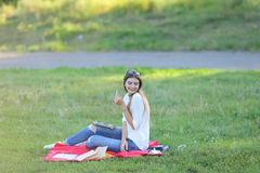 Η συνεδρίαση νέων κοριτσιών στη χλόη στο πάρκο λειτουργεί σε ένα lap-top και κατανάλωση του γρήγορου φαγητού Στοκ Φωτογραφία