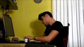 Η συνεδρίαση νεαρών άνδρων στο γραφείο που χρησιμοποιεί ένα PC ταμπλετών και το κύτταρο τηλεφωνούν, πίνοντας τον καφέ απόθεμα βίντεο