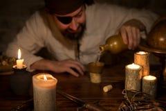 Η συνεδρίαση πειρατών σε έναν πίνακα και χύνει έξω το ρούμι, έννοια themeparty α Στοκ Εικόνες