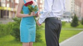 Η συνεδρίαση του ζεύγους για μια ημερομηνία, δόσιμο νεαρών άνδρων κόκκινο ανήλθε στην όμορφη φίλη του φιλμ μικρού μήκους