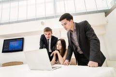 Η συνεδρίαση τριών επιχειρηματιών στον πίνακα και κάθεται και προσέχει την εργασία Στοκ Εικόνα