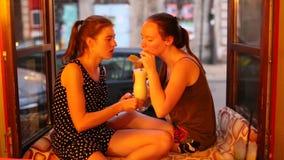 Η συνεδρίαση φίλων δύο κοριτσιών στο windowsill σε μια λέσχη νύχτας και πίνει τα κοκτέιλ απόθεμα βίντεο