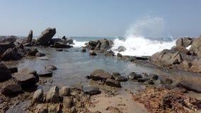 Η συντριβή κυμάτων πέρα από τους βράχους και γεμίζει το tidepool 2 φιλμ μικρού μήκους