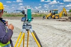 Η συσκευή Geodesist, λειτουργεί με το συνολικό σταθμό σε ένα Si οικοδόμησης Στοκ εικόνα με δικαίωμα ελεύθερης χρήσης