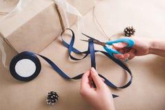 Η συσκευασία παρουσιάζει Χέρια με την κορδέλλα περικοπών ψαλιδιού Στοκ φωτογραφία με δικαίωμα ελεύθερης χρήσης