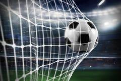 Η σφαίρα ποδοσφαίρου σημειώνει έναν στόχο στο δίχτυ Στοκ Φωτογραφία