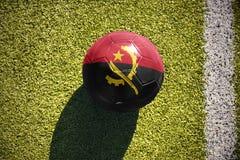 Η σφαίρα ποδοσφαίρου με τη εθνική σημαία της Ανγκόλα βρίσκεται στον τομέα Στοκ εικόνες με δικαίωμα ελεύθερης χρήσης