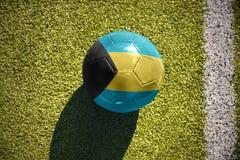 Η σφαίρα ποδοσφαίρου με τη εθνική σημαία των Μπαχαμών βρίσκεται στον τομέα Στοκ φωτογραφία με δικαίωμα ελεύθερης χρήσης