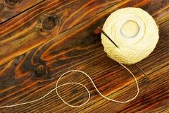 Η σφαίρα του νήματος και μια βελόνα σε ένα ξύλινο σχέδιο υποβάθρου Νήματα και ράφτης βελόνων για την κεντητική, ράψιμο, πλέκοντας στοκ εικόνα με δικαίωμα ελεύθερης χρήσης