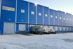 Η σύγχρονη αποθήκη εμπορευμάτων έξω, φορτηγά ξεφορτώνεται στις αποβάθρες φόρτωσης, Στοκ Εικόνα