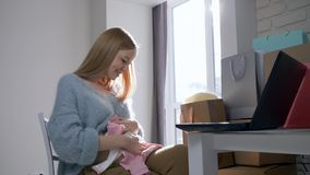 Η σύγχρονη εγκυμοσύνη, γυναίκα μητρότητας με τη γυμνή κοιλιά που εξετάζει τα νέα ενδύματα για το μελλοντικό παιδί αγόρασε στη συν απόθεμα βίντεο
