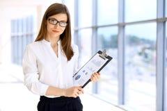 Η σύγχρονη επιχειρησιακή γυναίκα που στέκεται και που κρατά τα έγγραφα στο γραφείο με το αντίγραφο χωρίζει κατά διαστήματα την πε Στοκ φωτογραφίες με δικαίωμα ελεύθερης χρήσης