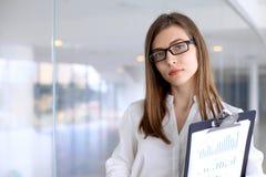 Η σύγχρονη επιχειρησιακή γυναίκα που στέκεται και που κρατά τα έγγραφα στο γραφείο με το αντίγραφο χωρίζει κατά διαστήματα την πε Στοκ φωτογραφία με δικαίωμα ελεύθερης χρήσης