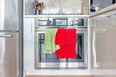 Η σύγχρονη, σύγχρονη σόμπα χρωμίου και ο φούρνος κυμαίνονται, με το ρολόι οθόνης χρώματος, και τις πράσινες και κόκκινες πετσέτες στοκ εικόνα με δικαίωμα ελεύθερης χρήσης