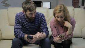 Η σύζυγος και ο σύζυγος επικοινωνούν εξετάζοντας τα smartphones οικογενειακή ζωή concepte απόθεμα βίντεο