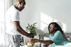 Η σύζυγος λαμβάνει την ανθοδέσμη λουλουδιών από το σύζυγό της στοκ εικόνες