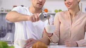 Η σύζυγος που φιλά το σύζυγό της στο ρητό μάγουλων σας ευχαριστεί για το φρέσκο καφέ πρωινού φιλμ μικρού μήκους