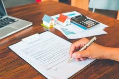 Η σύμβαση σπιτιών, άτομο υπογράφει μια σύμβαση για να αγοραστεί ένα σπίτι με ένα ρ στοκ φωτογραφίες με δικαίωμα ελεύθερης χρήσης
