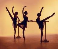 Η σύνθεση από τις σκιαγραφίες τριών νέων χορευτών στο μπαλέτο θέτει σε ένα πορτοκαλί υπόβαθρο Στοκ Εικόνες