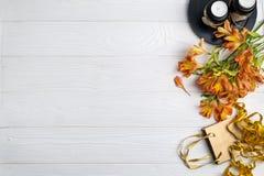 Η σύνθεση με την τσάντα δώρων ανθίζει και υπόβαθρο δώρων κεριών με το διάστημα για το κείμενο στοκ φωτογραφία