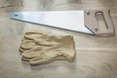 Η σύνθεση της ασφάλειας φορά γάντια στο ανοξείδωτο handsaw στον ξύλινο πίνακα con στοκ εικόνες με δικαίωμα ελεύθερης χρήσης